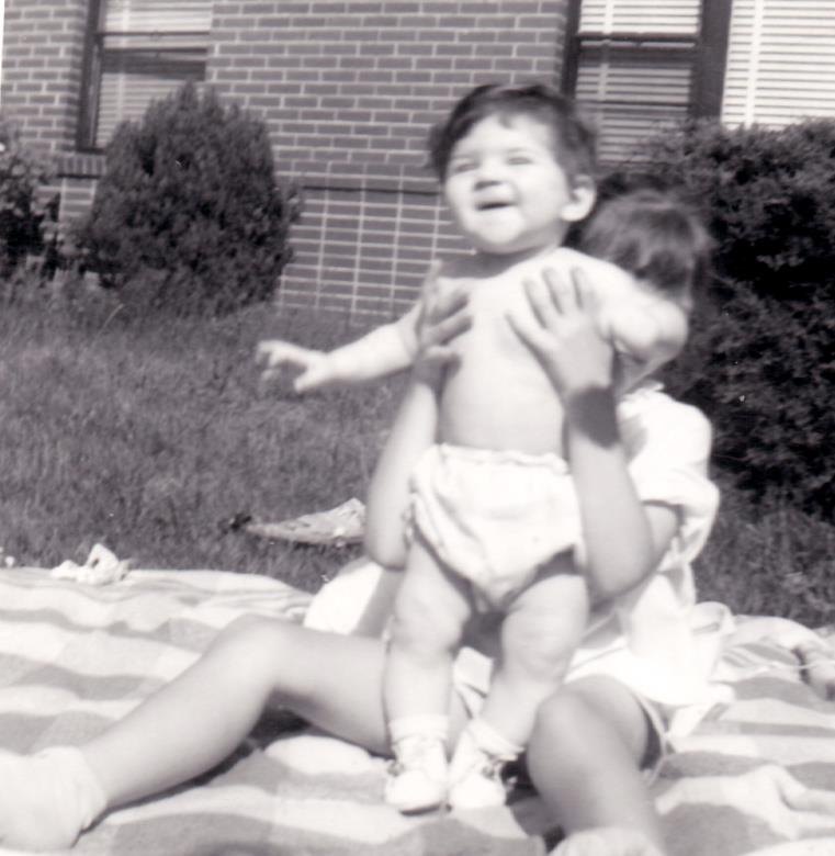 Baby Rhonda with a neighbor on a blanket in the yard laughing