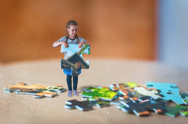 Child holding a puzzle piece of home